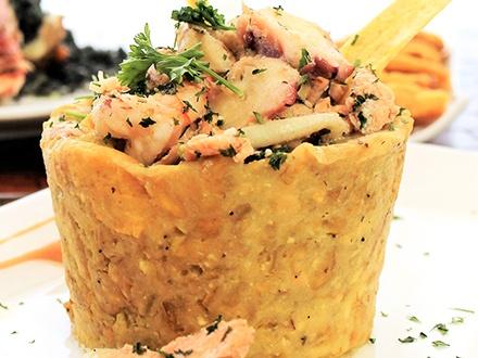 ¡Un menú costero para 2 personas! $27 por 2 Platos principales a escoger entre: Mofongo relleno de mariscos surtidos (camarones, pulpo, carrucho y pescado) o Chillo frito relleno de risotto o paella tinta de calamares + 1 Complemento a escoger entre: tostones, maduros, papas fritas o vegetales  + 2 Copas de vino tinto o blanco + 1 Postre Tiramisu o Cheesecake para compartir