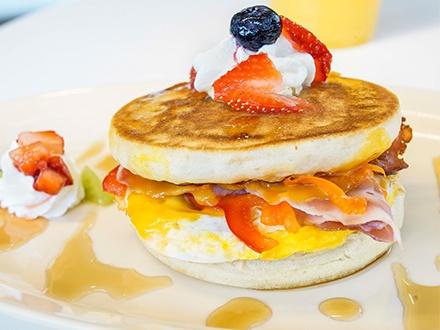 ¡Desayunos deliciosos a cualquier hora! $10 por 3 Pancakes Sandwiches con jamón, queso y huevo + 3 Jugos de frutas a escoger entre: China y Cranberry