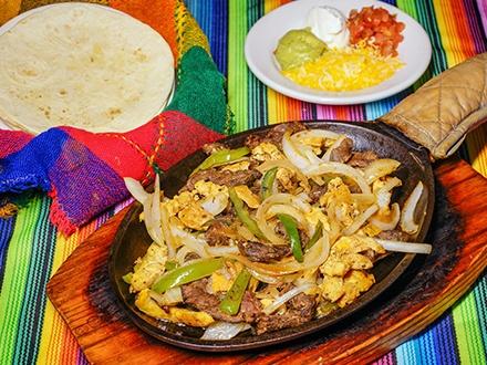 $34 por 2 Platos a elegir entre: Fajitas combinadas de res y pollo o Burrito gratinado de pollo, vegetariano, cerdo o res + 2 Margaritas, cervezas Corona, refrescos o agua + 1 Flan de queso o vainilla para compartir